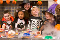 Four young friends and a woman at Halloween eating treats and smiling - PhotoDune Item for Sale