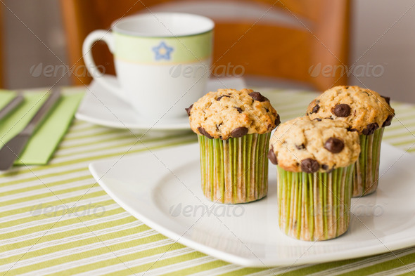 PhotoDune Chocolate chip muffins on white plate and green striped tableclo 4112105