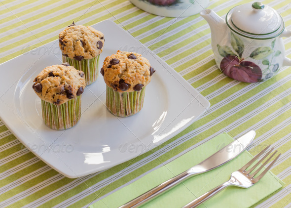 PhotoDune Chocolate chip muffins on white plate and green striped tableclo 4112109