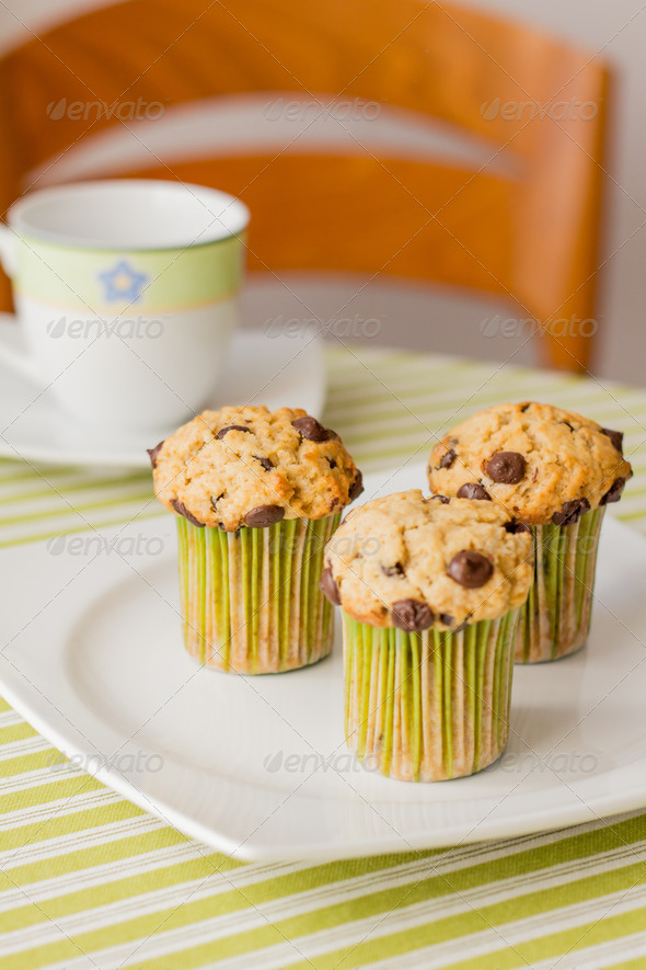 PhotoDune Chocolate chip muffins on white plate and green striped tableclo 4112108