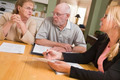 Senior Adult Couple Going Over Papers in Their Home with Agent. - PhotoDune Item for Sale