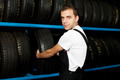 Young mechanic choosing tire in tire store - PhotoDune Item for Sale