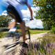 Cyclist in blurred motion riding on a rural road through green spring meadow  - PhotoDune Item for Sale