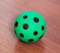 green ball with black spots on a wooden desk - PhotoDune Item for Sale