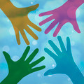 Team symbol. Happy colorful hands on a cloudy background - PhotoDune Item for Sale