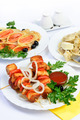 White table with food of meat, salmon rolls and dumplings. - PhotoDune Item for Sale