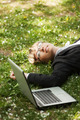 Happy business woman with laptop lying on the grass - PhotoDune Item for Sale