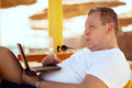 Man relaxing with a laptop at beach resort - PhotoDune Item for Sale