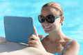 Young woman in a pool using tablet computer - PhotoDune Item for Sale
