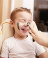 Little boy laughing as his mother paints his face - PhotoDune Item for Sale