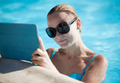 Young woman using a tablet poolside - PhotoDune Item for Sale