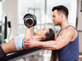 Personal trainer helping woman working with dumbbells - PhotoDune Item for Sale
