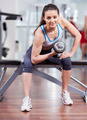 Athletic woman working her biceps with dumbbells at the gym - PhotoDune Item for Sale