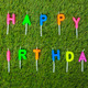 Colorful happy birthday candles on field - PhotoDune Item for Sale