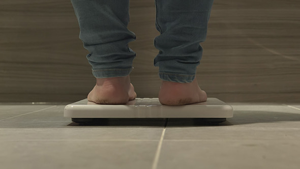 VideoHive Women Weighing Herself On Bathroom Scales 7384136