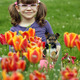 little girl with puppy in the tulip flower garden - PhotoDune Item for Sale